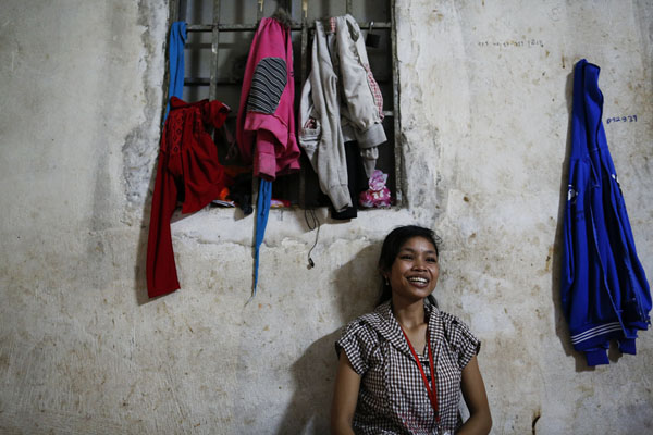 Maen Sopeak, a garment worker who shares a single room with six other girls smile during a lunch break in one of Phnom Penh's suburbs